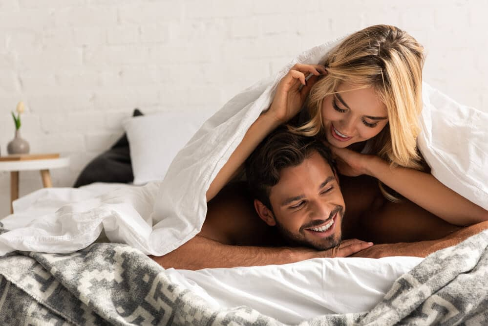 happy couple in bed after sex