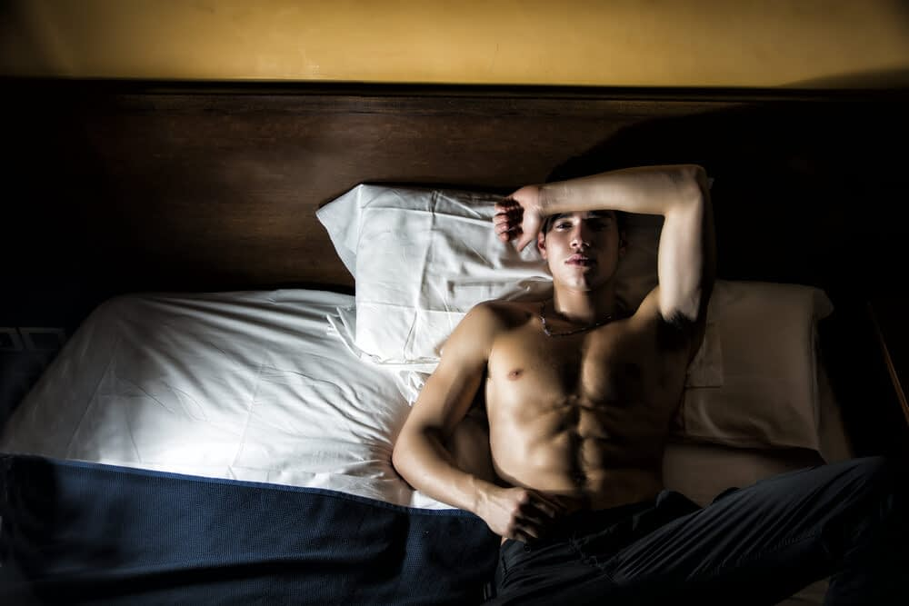 man exhausted bed