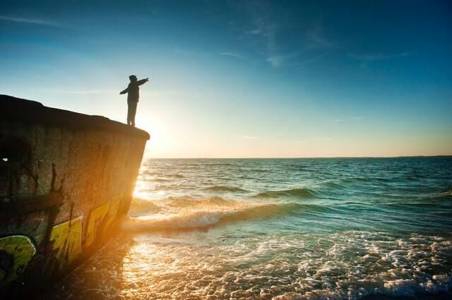 man on cliff getting sunshine