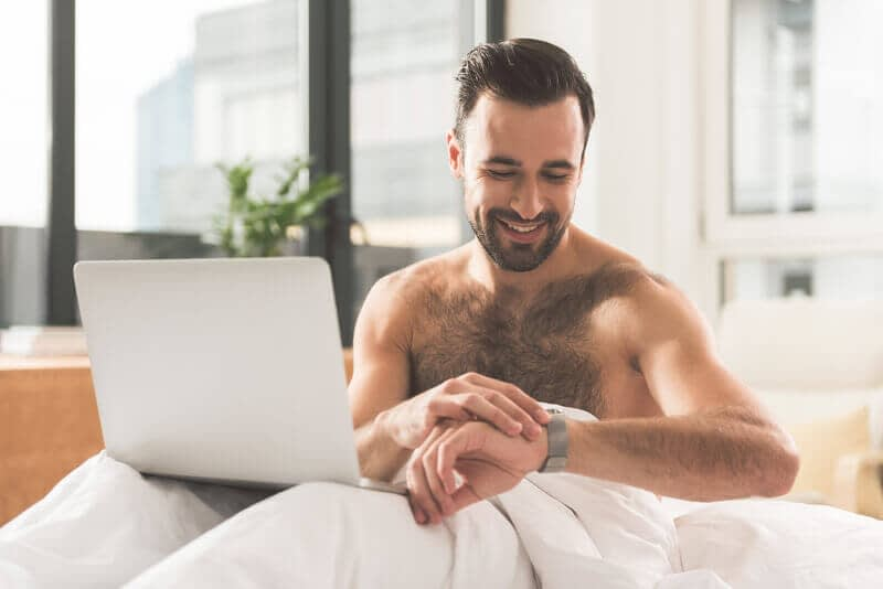 man watching pornography in bed