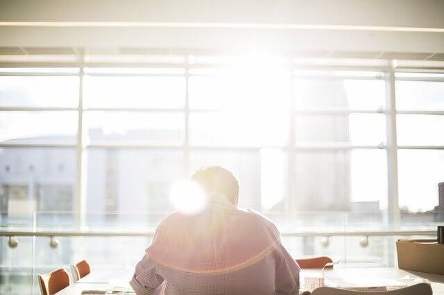 man working inside a building sunshine outside