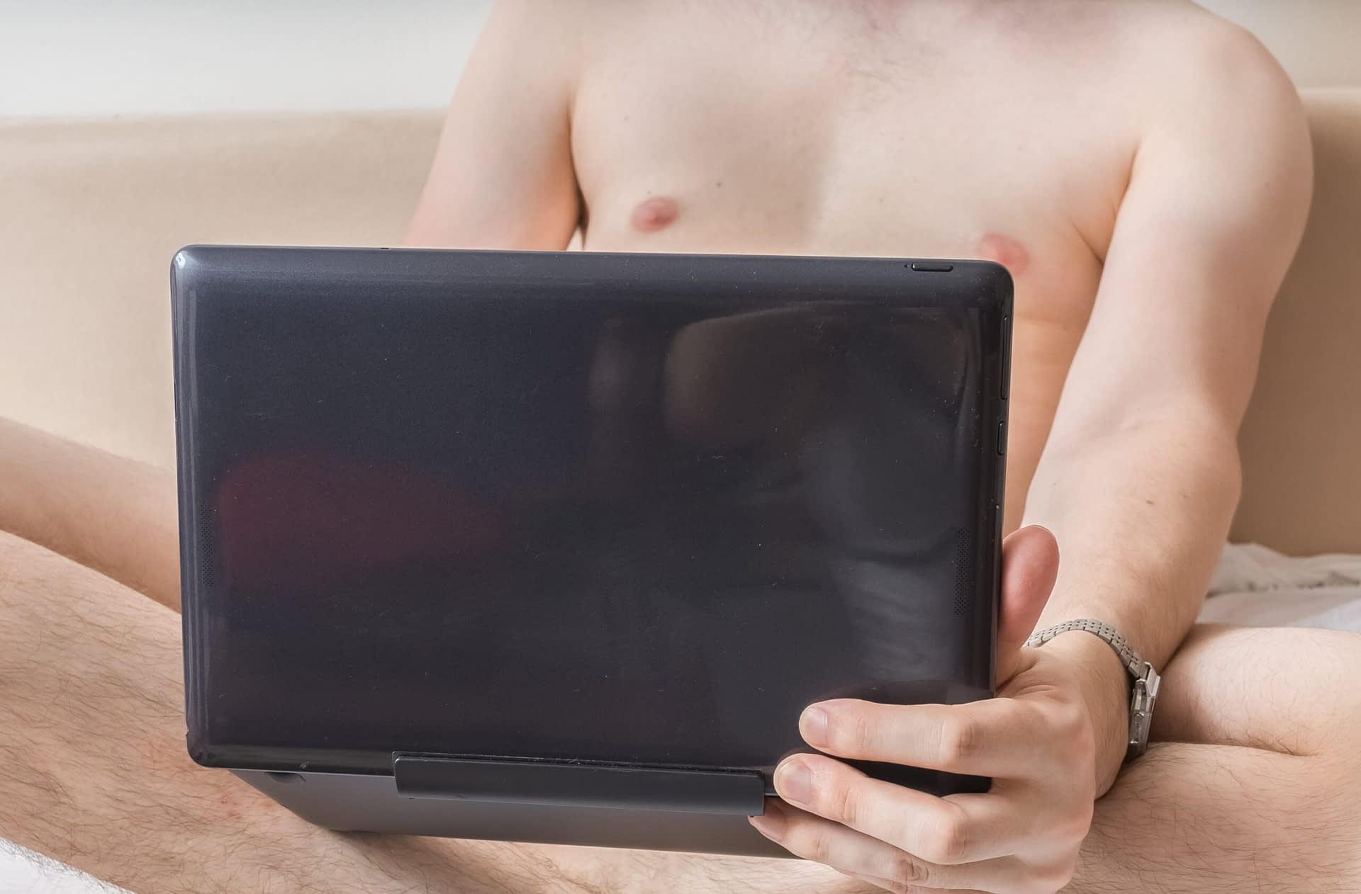 young naked man is watching pornography on laptop and masturbating